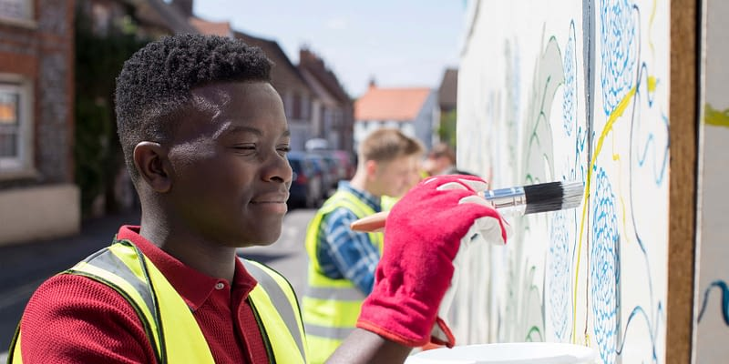 community volunteers painting a wall